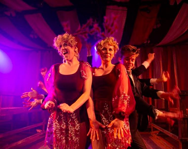 multiple performers dancing in dim lit room