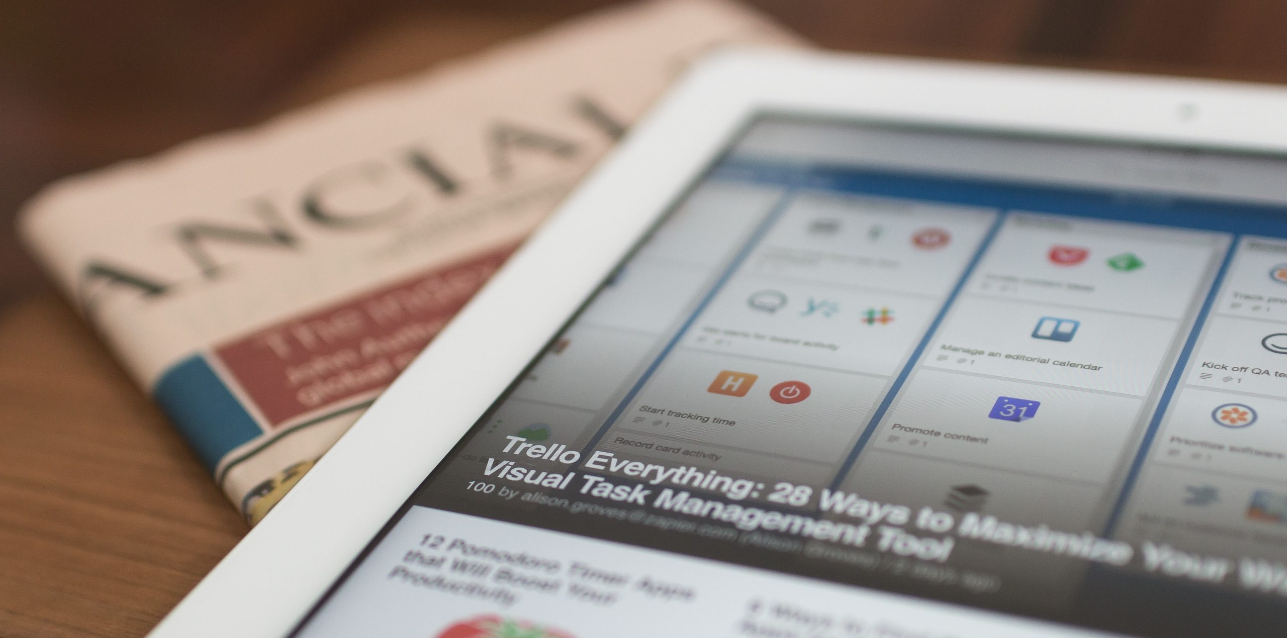 white tablet on top of newspaper